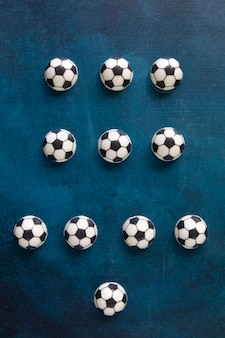The most popular scheme of football players positions on the field from chocolate cakes in the form of footballs on a beautiful blue table - top view, illustration