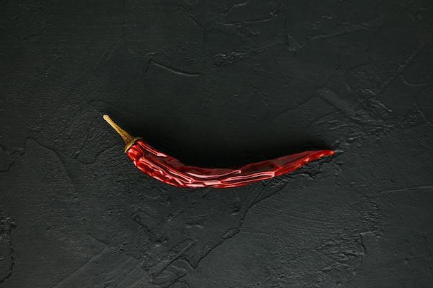 Most popular spicy herb for thai food dried fruit of capsicum frutescens whole dry red chili hot pepper on black stone background spices and seasonings for cooking top view soft focus