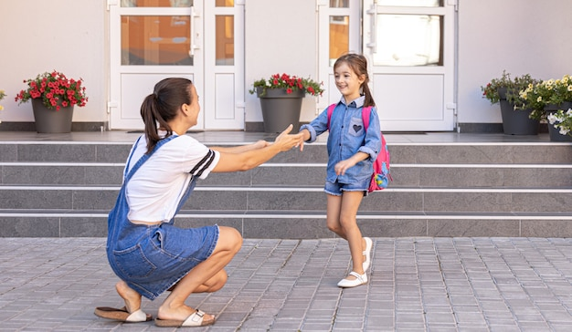 A mother accompanies student to school, happy little girl with a caring mom, back to school.