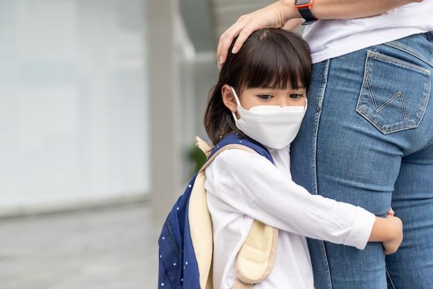어머니는 아이를 학교에 동반합니다. 엄마는 학생을 지원하고 동기를 부여합니다. 마스크를 쓴 어린 소녀는 어머니를 떠나고 싶지 않습니다. 초등학교를 두려워합니다.