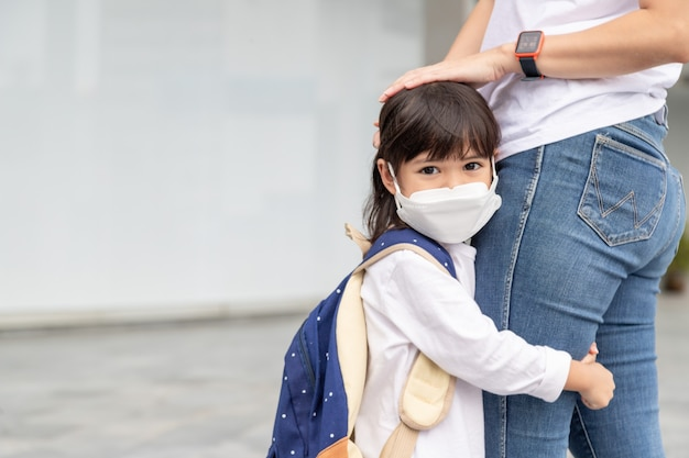 母は子供を学校に連れて行く。お母さんは生徒をサポートし、やる気を起こさせます。フェイスマスクをかぶった少女は母親から離れたくない。小学校を恐れています。