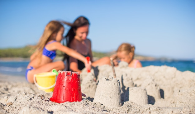 Mother and adorable little daughters playing with beach toys