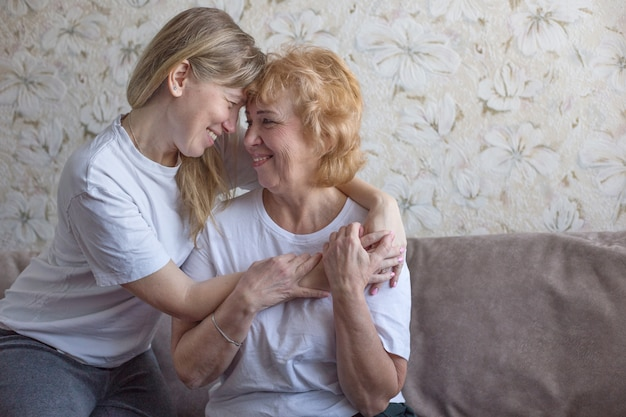 Mother and adult blonde daughter in white t-shirts hug on couch and laugh. mother's day concept