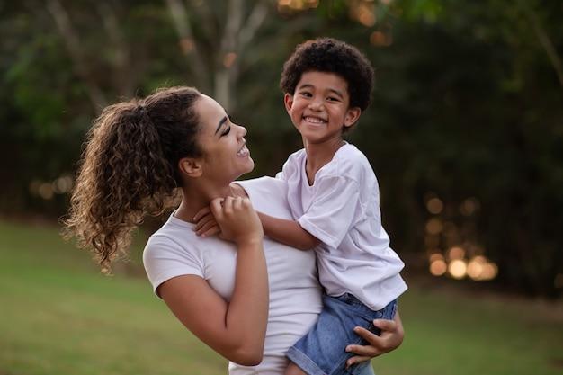 공원에서 카메라를 보며 웃고 있는 엄마와 아프리카 아들