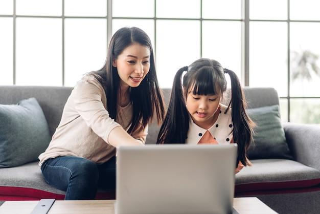 Мать и азиатский ребенок маленькая девочка учится и смотрит на портативный компьютер, делая домашнее задание, изучая знания с помощью системы электронного обучения онлайн. детская видеоконференция с учителем-наставником дома