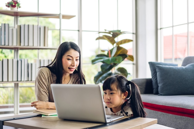 母とアジアの子供は、オンライン教育のeラーニングシステムで知識を勉強する宿題を作るラップトップコンピューターを学び、見ています。自宅で教師の家庭教師との子供たちのビデオ会議