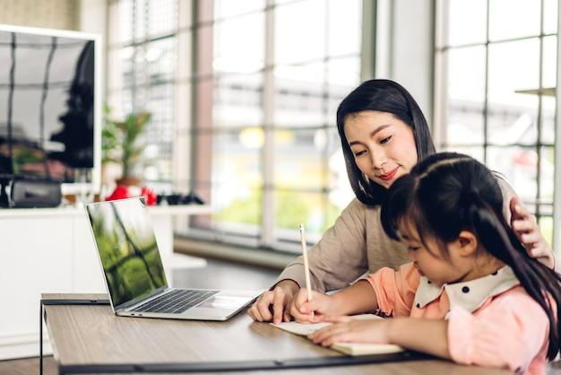 オンライン教育のeラーニングシステムで知識を勉強する宿題を作るラップトップコンピューターを学び、見ている母とアジアの子供小さな女の子