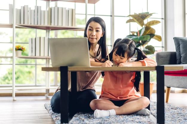 Мать и азиатский ребенок маленькая девочка учится и смотрит на портативный компьютер, делая домашнее задание, изучая знания с помощью системы электронного обучения онлайн