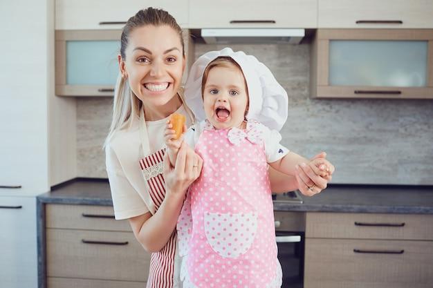 엄마와 아기는 부엌에서 음식을 준비하고 있습니다