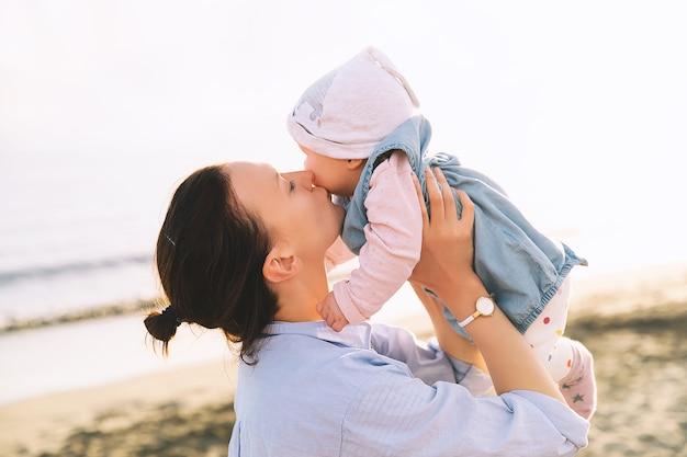 여름에 해변 바다에서 일몰에 엄마와 아기 행복한 가족 배경