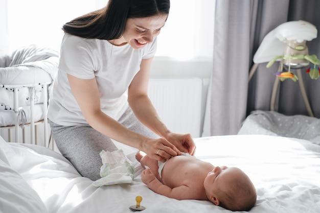 Мать и мальчик меняют подгузник после сна