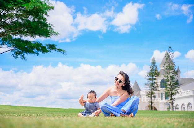 어머니 및 아기 소년 잔디에 재생
