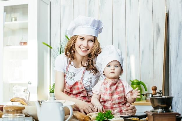 행복하고 아름다운 엄마와 아기 딸 집에서 부엌에서 과자와 밀가루를 준비