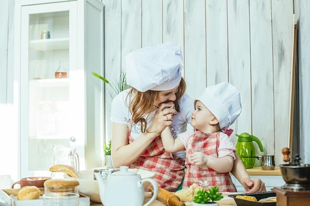 엄마와 아기 딸이 행복하고 아름답게 집에서 부엌에서 패스트리와 밀가루를 준비합니다