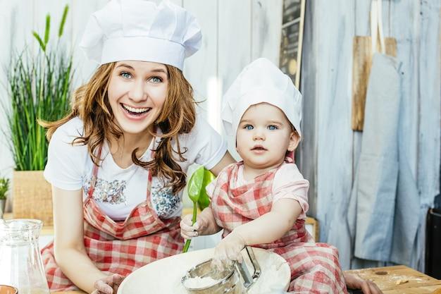 엄마와 아기 딸이 행복하고 아름답게 집에서 부엌에서 패스트리와 밀가루를 준비합니다 프리미엄 사진
