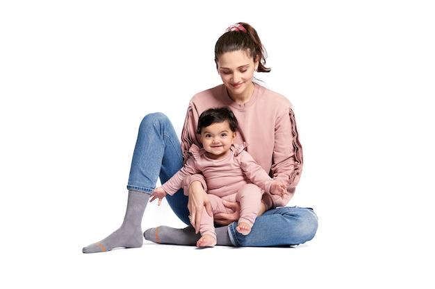 흰 벽에 고립 된 어머니 및 아기 딸