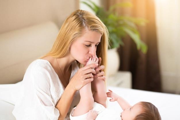白いベッドの上の母と女の赤ちゃん。自宅の日当たりの良い寝室で遊ぶママとかわいい赤ちゃん。一緒に楽しんでいる家族。彼女の娘の足にキスする若い母親