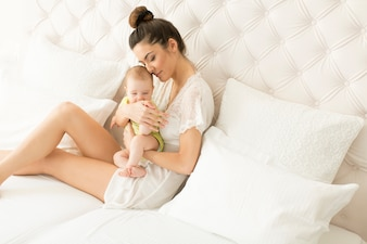Mother and baby girl on the bed