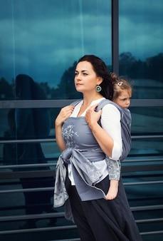 母と女の赤ちゃんは、反射、現代の家族と都市のガラスの近くに灰色のラップスリング滞在で座っています