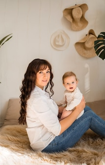 엄마와 아기 소녀는 소파에 옆으로 앉아