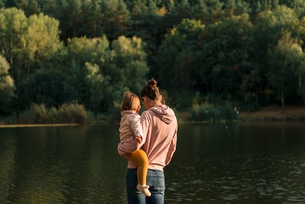 호수 근처에 앉아 어머니 및 아기 소녀입니다. 현지 여행. 새로운 정상적인 휴가. 어머니의 날