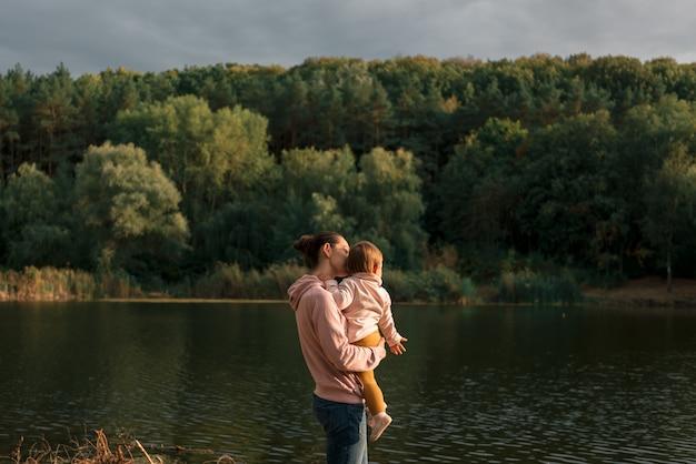 湖の近くに座っているママとベビーの女の子。ローカル旅行。新しい通常の休暇。母の日