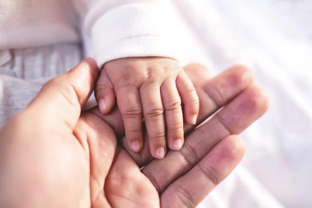 Рука матери и младенца на белой предпосылке ткани.
