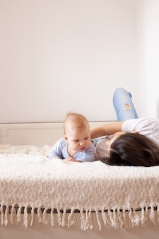 ベッドの中で母と赤ちゃん。生まれたばかりの息子と遊ぶ若いお母さん。家で一緒に子供と親。朝の子供連れの家族。日当たりの良い寝室で子供とリラックスした女性。幸福と母性