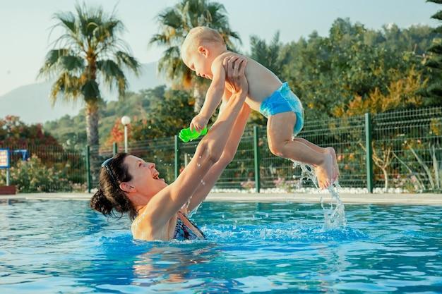 屋外スイミングプールでの母と赤ちゃん水泳を学ぶ子供ママと子供が水で遊ぶ家族の夏休み子供のためのアクティブで健康的なスポーツ
