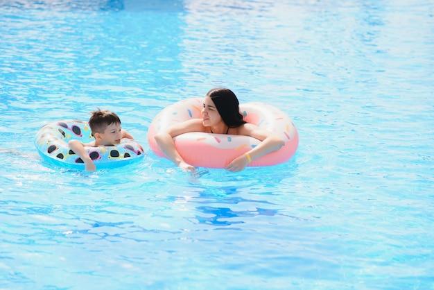 열대 리조트의 야외 수영장에서 엄마와 아기. 물에서 노는 엄마와 아이.