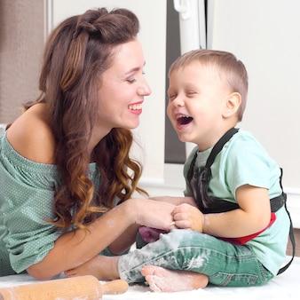 キッチンで生地を作っている間、母と赤ちゃんは笑います。家庭での親子関係が大好き