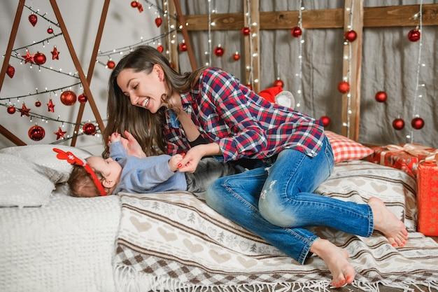 Мать и ребенок лежат на кровати. мать и ее мальчик дома.