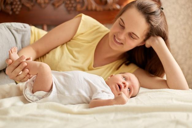 白い毛布の上でベッドに横になっている母親と赤ちゃん、黄色いtシャツを着たママの笑顔、生まれたばかりの子供との時間を楽しんでいる、乳児は外向きのことを勉強するために目をそらしています。