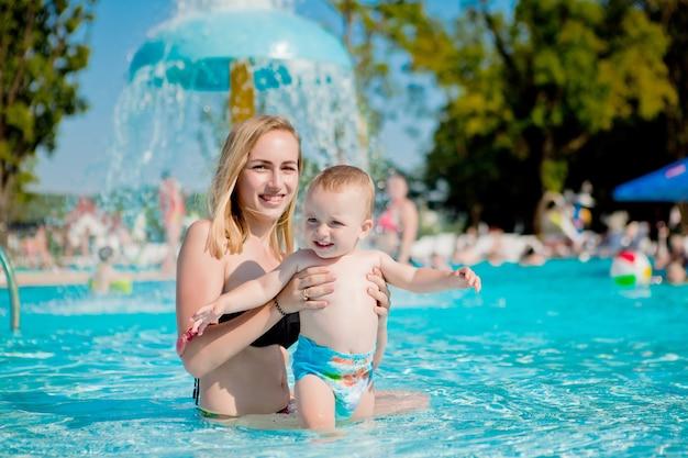Мать и ребенок играют в бассейне