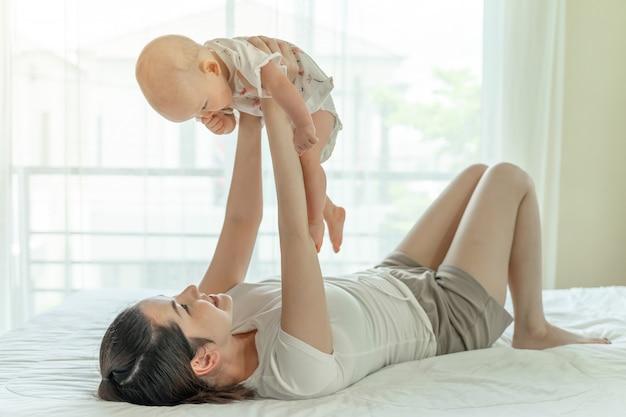 Мать и ребенок играют в кровати