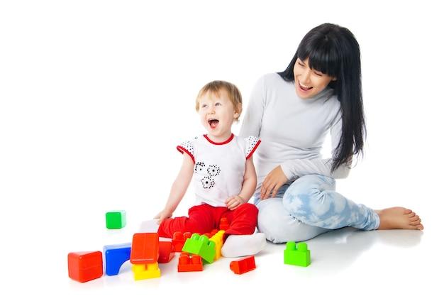 흰색으로 격리된 빌딩 블록 장난감을 가지고 노는 엄마와 아기