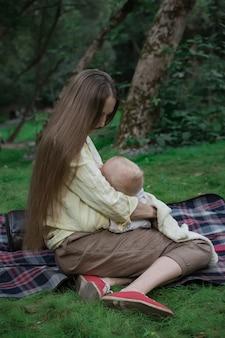 ピクニック毛布で公園でリラックスした母と赤ちゃん。幸せな家族の概念。垂直フレーム。