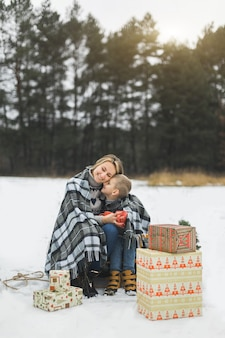 冬の森の木製のそりに座って、熱いお茶を飲む母と赤ちゃん