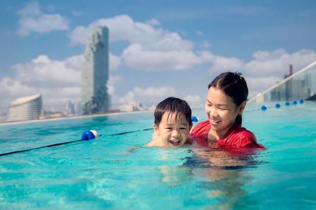 Мать и ребенок плавают в бассейне
