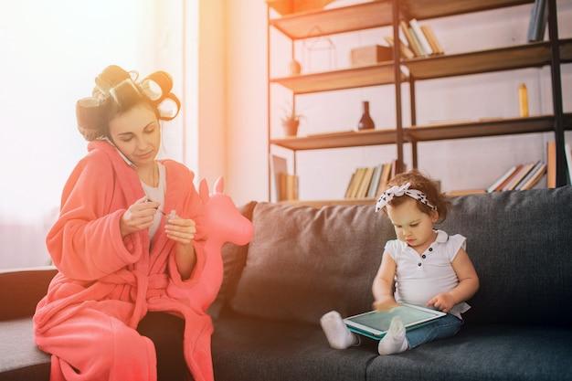 母親と赤ちゃんが一緒に家事アイロンをかけています。宿題をしている主婦と子供