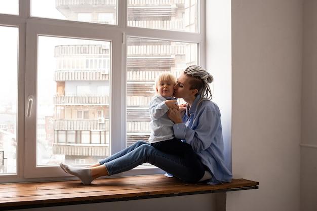 격리 시간에 창에 앉아 어머니와 소년 아이