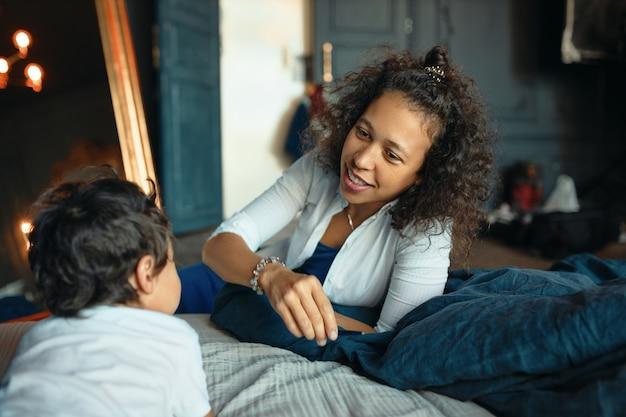 寝室での母と子の絆。彼女の幼い息子と一緒に家でリラックスする幸せな思いやりのある若い混血の女性