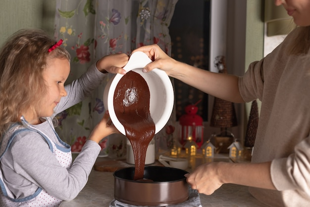 一緒にクリスマスチョコレートケーキを調理する母と子の娘