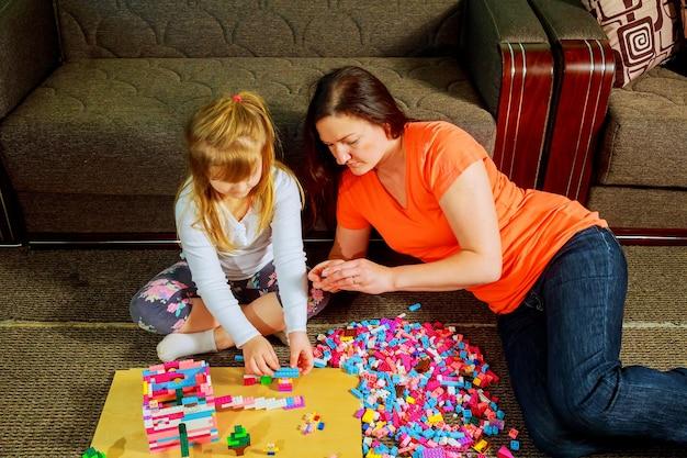 Мать и дочка ребенка играют вместе, строят из конструктора. милая мама играет вместе в помещении. молодая мама с ребенком играют вместе