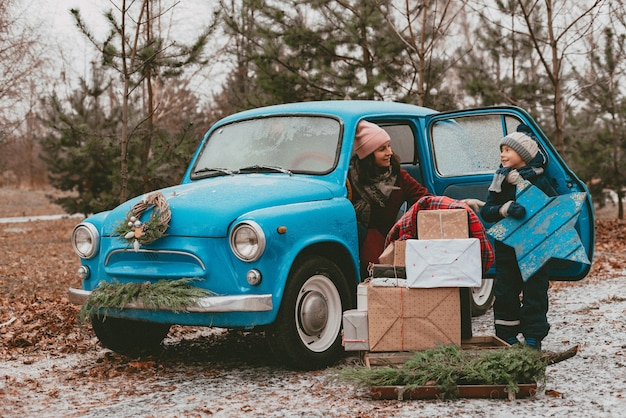 어머니와 아이 축제 크리스마스 트리 분기, 선물 상자 공예 포장지, 화환 소나무 전나무 바늘이있는 파란색 복고풍 자동차로 장식되어 있습니다. 새해 가족 여행. 어린 시절의 꿈, 추억의 욕망.
