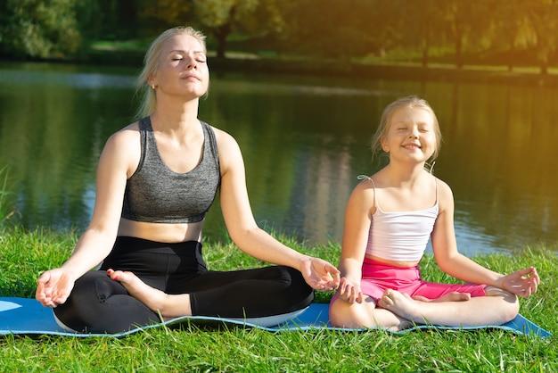 Мать и ребенок занимаются йогой, медитируя на траве в позе лотоса. мать и маленькая девочка занимаются йогой в городском парке.
