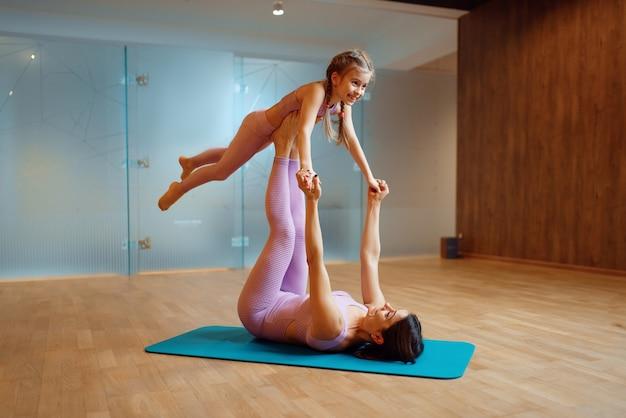 Мать и ребенок вместе делают упражнения на коврике в тренажерном зале, занимаются йогой, гимнастикой. мама и маленькая девочка в спортивной одежде, совместные тренировки в спортивном клубе