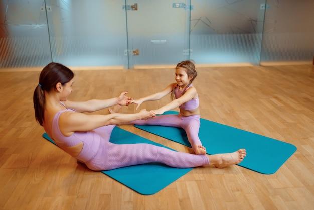 Мать и ребенок делают упражнения на растяжку на ковриках в тренажерном зале, тренировки пилатеса, гимнастики. мама и маленькая девочка в спортивной одежде, совместные тренировки в спортивном клубе