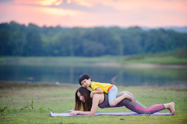 Мать и ребенок делают упражнения йоги на траве в парке перед закатом летом.
