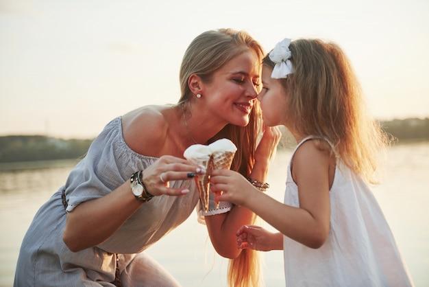 Мать и ребенок едят мороженое в парке на закате.